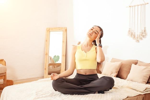Zdrowy tryb życia. kobieta ćwiczy jogę na swoim domowym łóżku. poranne ćwiczenie.