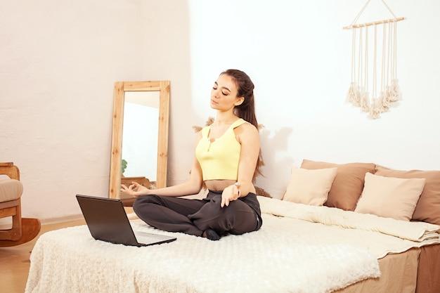 Zdrowy tryb życia. kobieta na łóżku. poranne ćwiczenia online z laptopem.