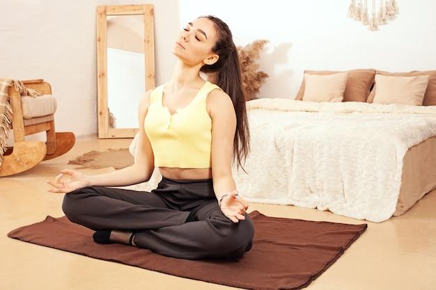 Zdrowy tryb życia. kobieta uprawia jogę, siedzi w pozycji lotosu. domowa kwarantanna, mata, ćwiczenia