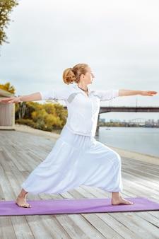Zdrowy tryb życia. młoda kobieta praktykuje jogę podczas porannych ćwiczeń na świeżym powietrzu