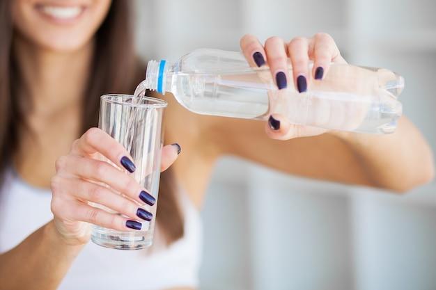 Zdrowy tryb życia. piękna dysponowana młoda kobieta trzyma butelkę woda