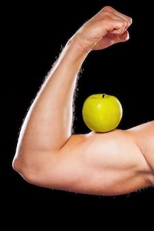 Zdrowy tryb życia. przycięty obraz muskularnego mężczyzny pokazującego swoje idealne bicepsy z zielonym jabłkiem na białym tle na szarym tle
