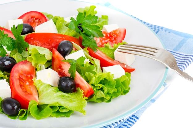 Zdrowy tryb życia. sałatka jarzynowa z oliwkami i kozim serem na białym tle