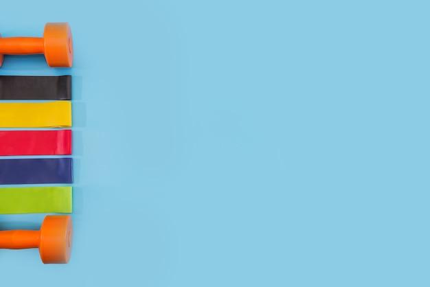 Zdrowy tryb życia, sprzęt sportowy i sportowy. hantle i kolorowe gumki do fitnessu na niebieskim tle. skopiuj miejsce. miejsce na twój tekst.
