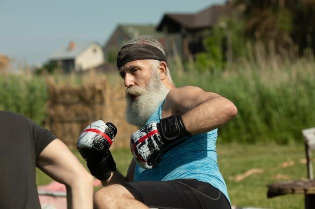 Zdrowy wojownik brodaty starszy staruszek rękawice bokserskie.