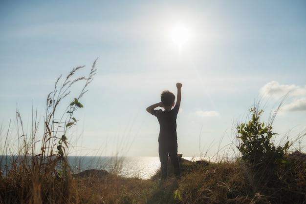 Zdrowy wysportowany chłopiec podnoszący rękę po dotarciu na szczyt górski pieszymi wędrówkami