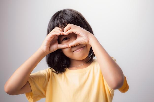 Zdrowy wzrok i oczy portret uśmiechniętego azjatyckiego dziecka z rękami w kształcie serca na oczach