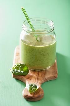 Zdrowy zielony koktajl ze szpinakiem mango-bananem w szklanych słoikach