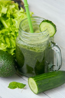 Zdrowy zielony smoothie z składnikami na białym drewnianym tle
