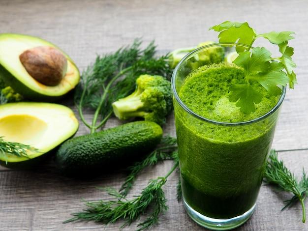 Zdrowy zielony sok warzywny na drewnianym stole