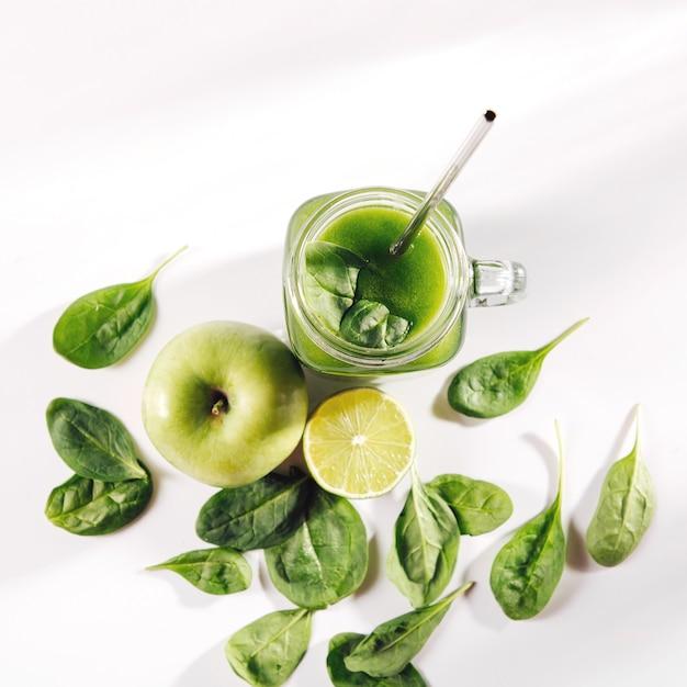 Zdrowy zielony sok warzywny ze szpinakiem i zielonymi owocami i warzywami na białym stole.