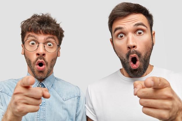 Zdumieni dwaj brodaci faceci mają zaskoczone miny, wskazują, mają przerażone miny, stoją ramię w ramię pod białą ścianą, zauważają coś niesamowitego w oddali