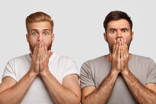 Zdumieni, wzruszeni brodaci faceci zakrywają usta dłońmi, ubrani w zwykłe ciuchy, czują się zdumieni oglądając horror, odizolowani na białej ścianie. koncepcja ludzi i mimiki