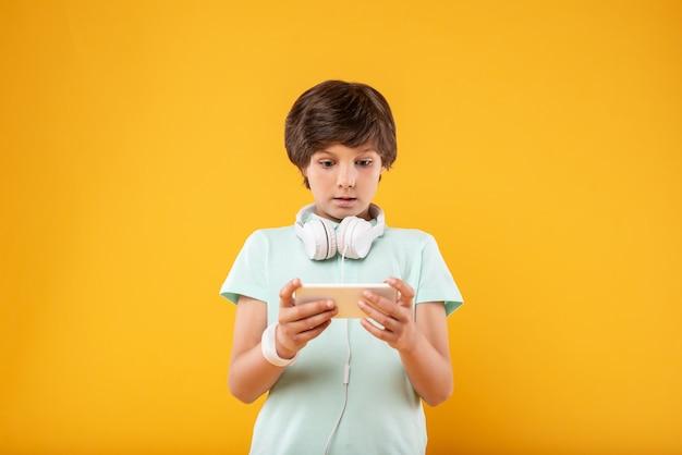 Zdumienie. zaskoczony ciemnowłosy uczeń korzystający z telefonu i noszący słuchawki
