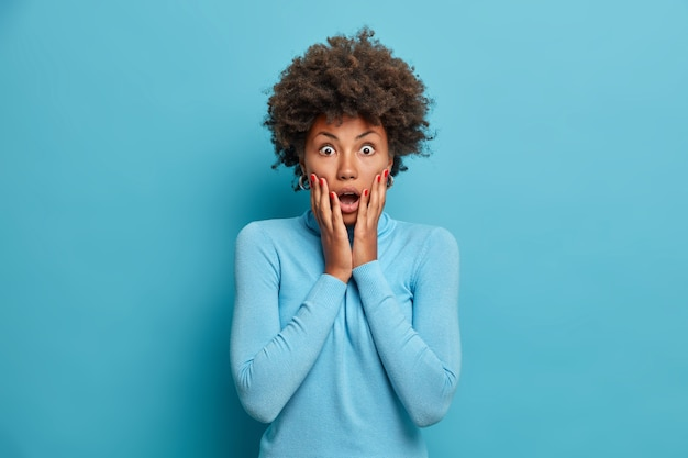 Zdumiona ciemnoskóra afroamerykanka chwyta twarz i stoi oniemiały z szeroko otwartymi ustami