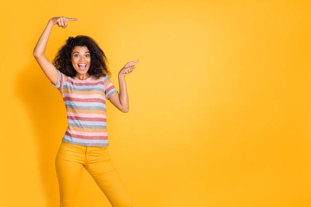 Zdumiona ciemnoskóra dziewczyna wskazująca dwoma palcami wskazującymi na żółtym tle