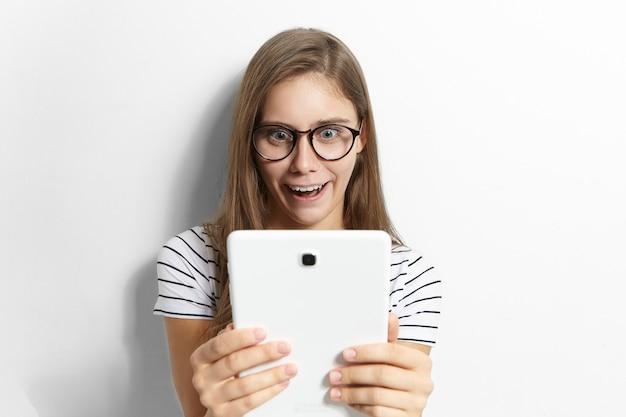 Zdumiona emocjonalna zabawna nastolatka w stylowych okularach trzymająca ogólny cyfrowy tablet i szeroko otwierająca usta, zszokowana podczas czytania wiadomości lub oglądania szokujących treści w internecie