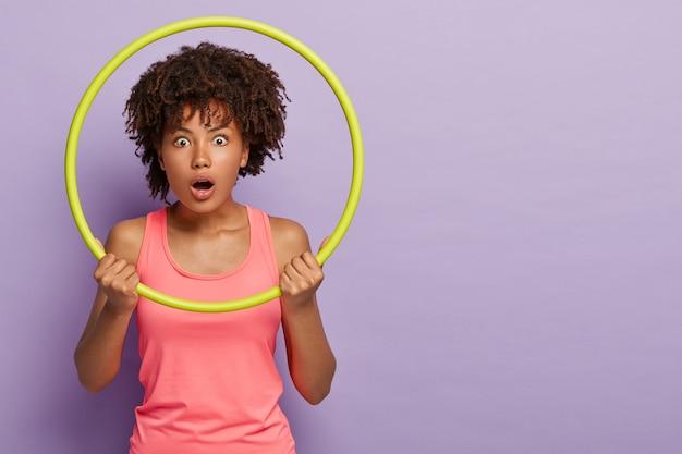 Zdumiona fitness dziewczyna z kręconymi fryzurami, patrzy przez hula-hoop, ma otwarte usta, ubrana w swobodną różową kamizelkę, wykonuje ćwiczenia sportowe