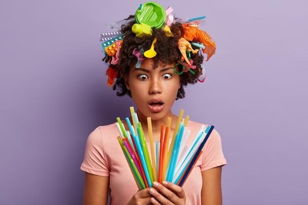 Zdumiona kobieta pozuje ze śmieciami we włosach