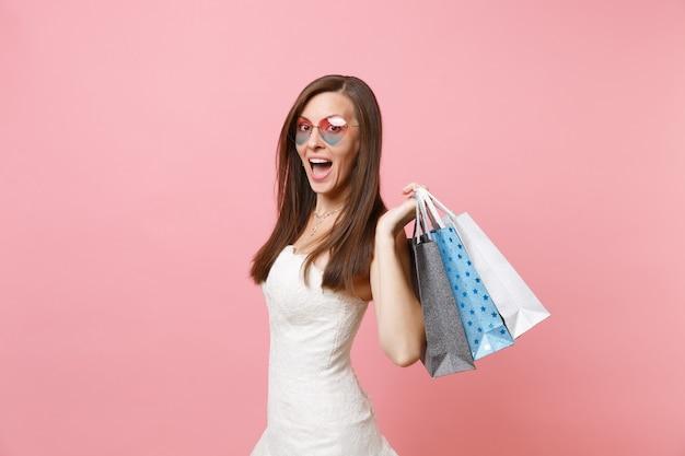 Zdumiona kobieta z otwartymi ustami w białej sukni, w okularach w kształcie serca, trzymająca wielokolorowe paczki torby z zakupami po zakupach
