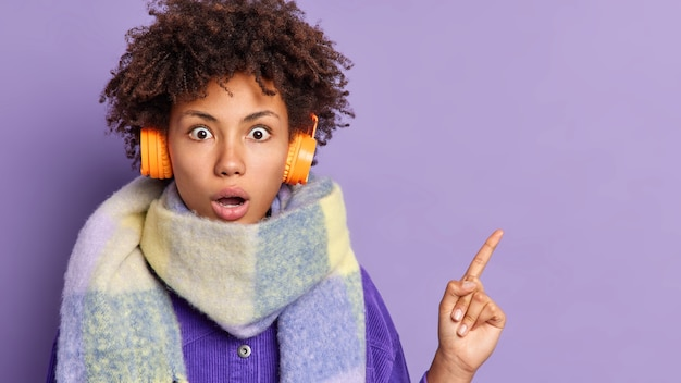 Zdumiona, kręcona dziewczyna tysiąclecia patrzy zaskakująco, co wskazuje, że w prawym górnym rogu pokazuje coś niesamowitego i zapierającego dech w piersiach nosi słuchawki stereo na uszach, szalik wokół szyi