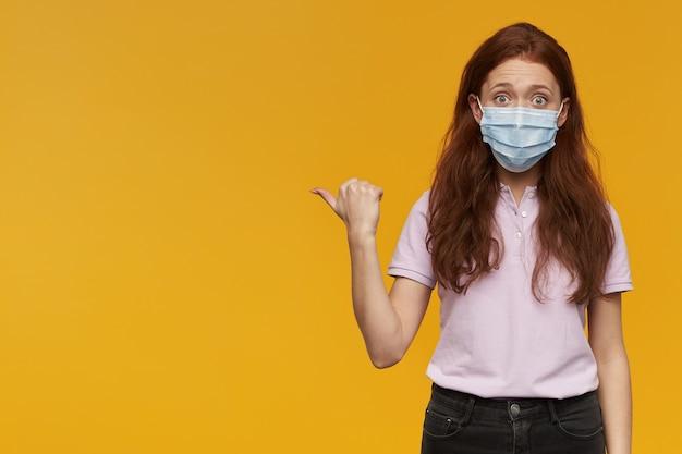 Zdumiona młoda kobieta nosząca medyczną maskę ochronną stojącą i wskazującą na bok w pustej przestrzeni odizolowanej nad żółtą ścianą
