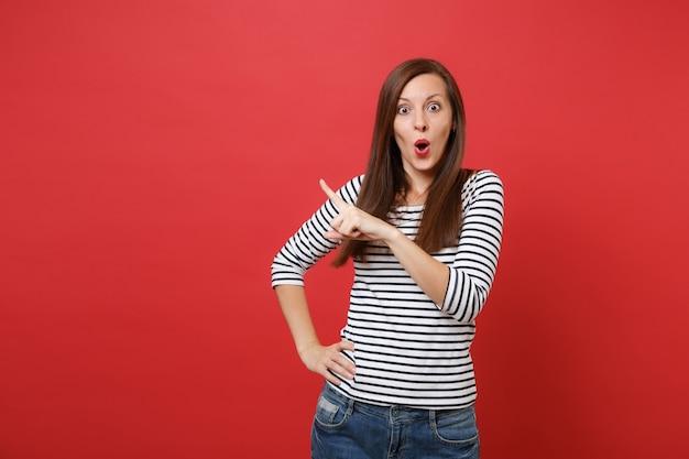Zdumiona młoda kobieta w pasiastych ubraniach, wskazując palcem na bok, trzymająca szeroko otwarte usta, wyglądająca na zaskoczoną