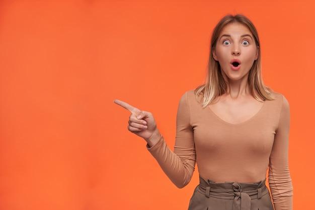 Zdumiona młoda, urocza, krótkowłosa blondynka ze zdumieniem okrąża swoje niebieskie oczy, wskazując palcem wskazującym na bok, stojąc nad pomarańczową ścianą