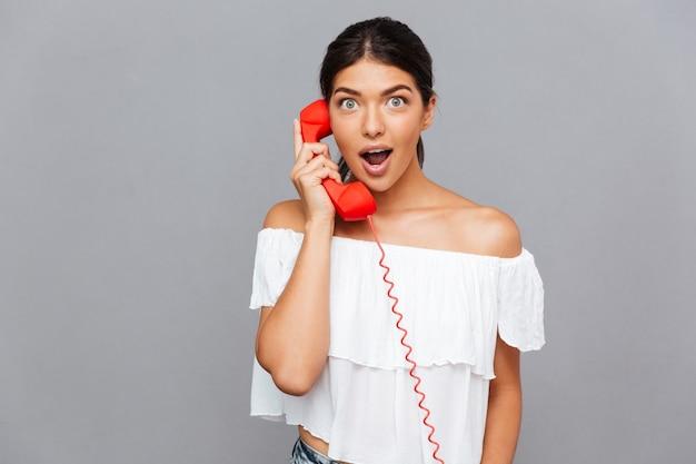Zdumiona piękna kobieta rozmawiająca przez rurkę telefoniczną odizolowaną na szarej ścianie