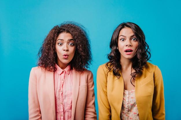 Zdumione kobiety stojące na jasnoniebieskiej ścianie