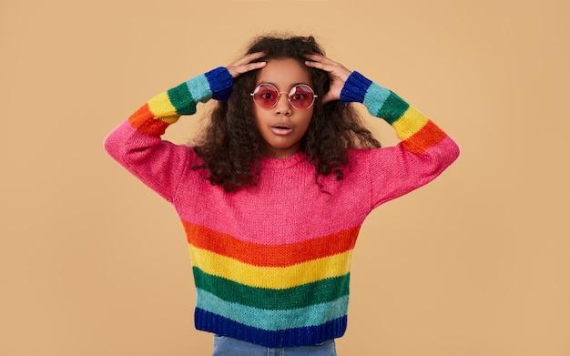 Zdumiony african american dziecko w tęczowym swetrze i okularach przeciwsłonecznych, trzymając się za ręce na głowie