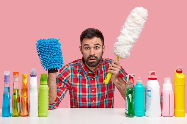 Zdumiony brodacz trzyma szczotkę do kurzu, mop, gapi się, dba o higienę w domu