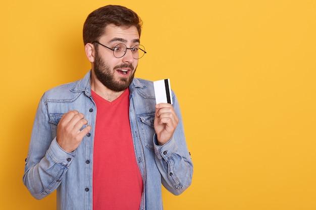 Zdumiony brodaty mężczyzna ubiera dżinsową kurtkę, czerwoną koszulę i okulary, trzymając w rękach kartę kredytową i wygląda na kartę z otwartymi ustami