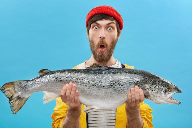 Zdumiony brodaty rybak ubrany niedbale, trzymający ogromną rybę z wyłupiastymi oczami i opadającą szczęką, zszokowany złowieniem takiego dużego pstrąga lub łososia.