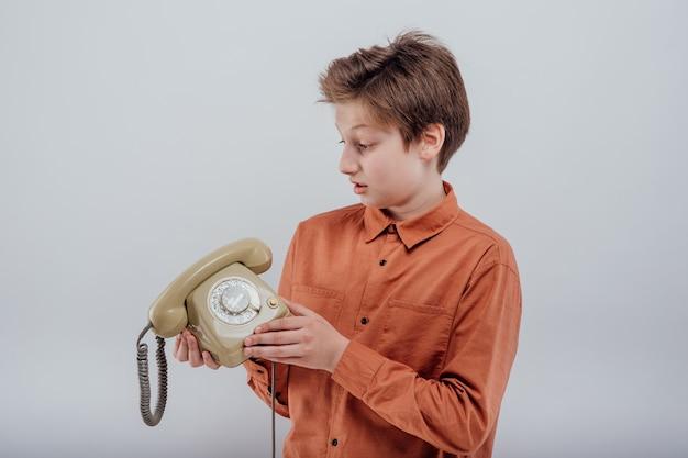 Zdumiony chłopiec dziecko ze starym widokiem profilu telefonu na białym tle