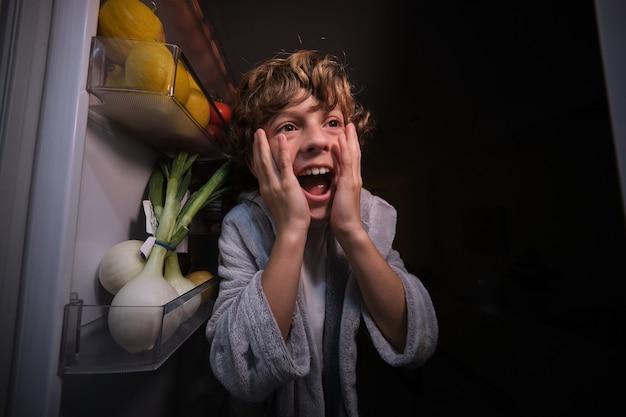 Zdumiony chłopiec przy lodówce z produktami w ciemnej kuchni
