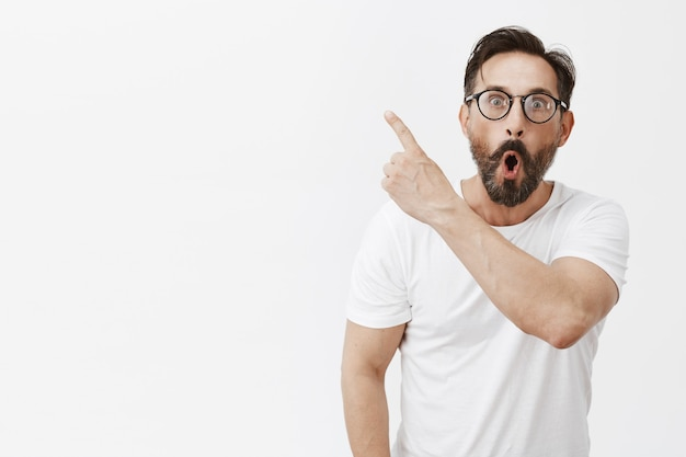 Zdumiony i zdumiony brodaty dojrzały mężczyzna w okularach pozowanie