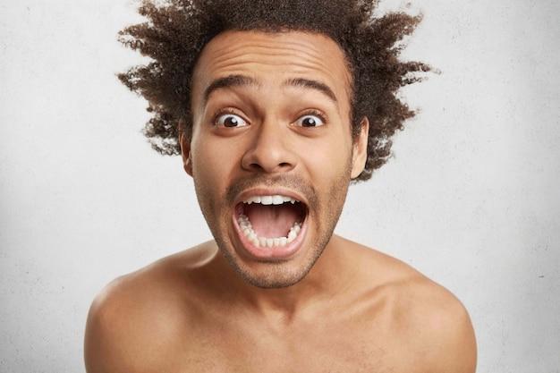 Zdumiony klient afro american z szeroko otwartymi oczami jest w szoku