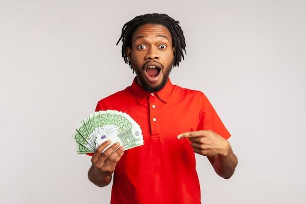 Zdumiony mężczyzna trzyma dużo pieniędzy, wskazując na banknoty euro, zszokowany nagłą wygraną.