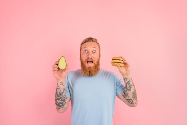 Zdumiony mężczyzna z brodą i tatuażami jest niezdecydowany, czy zjeść awokado, czy hamburgera