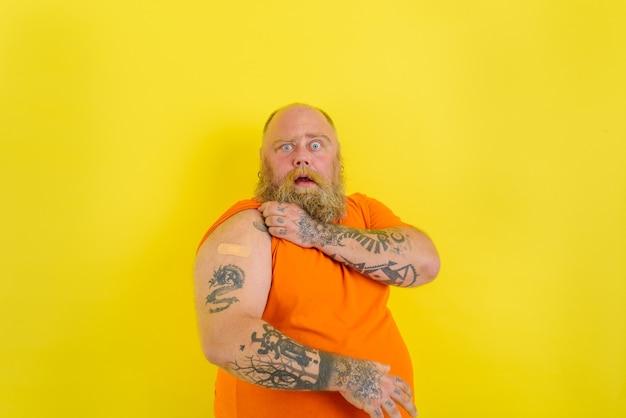 Zdumiony mężczyzna z brodą i tatuażami zrobił szczepionkę przeciwko covid