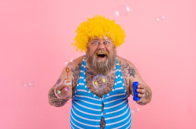 Zdumiony mężczyzna z żółtą peruką w głowie bawi się mydłem bąbelkowym