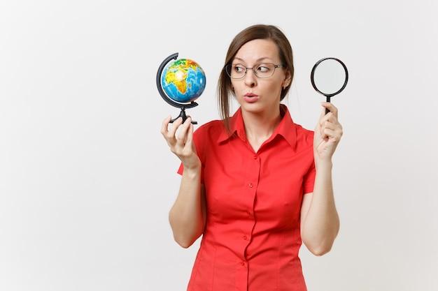 Zdumiony nauczyciel biznesu kobieta w czerwonej koszuli gospodarstwa i patrząc przez szkło powiększające na świecie na białym tle. nauczanie edukacji w koncepcji uniwersytetu liceum. skopiuj miejsce.