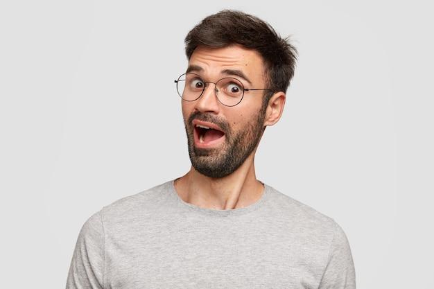Zdumiony nieogolony mężczyzna w okularach zastanawia się nad najnowszymi wiadomościami, nie może uwierzyć w plotki