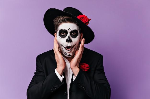 Zdumiony pan w kapeluszu z różą otworzył usta ze zdumienia. zbliżenie portret człowieka z pomalowaną twarzą na karnawał.