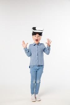 Zdumiony przyszłością. mała dziewczynka lub dziecko w dżinsach i koszuli z okularami zestaw słuchawkowy wirtualnej rzeczywistości na białym tle na tle białego studia. koncepcja najnowocześniejszych technologii, gier wideo, innowacji.