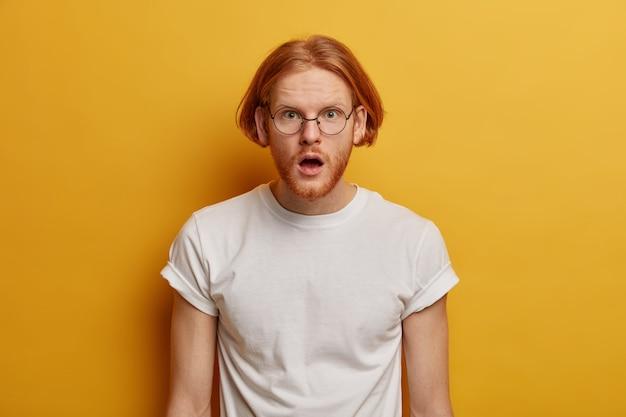 Zdumiony rudowłosy model ze zdumieniem otwiera usta