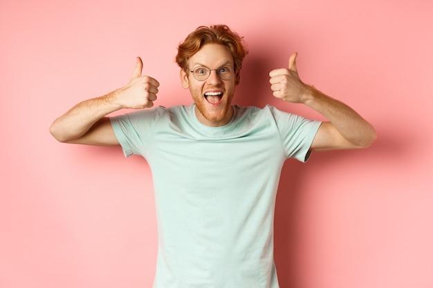 Zdumiony rudy facet krzyczy z radości i wygląda na podekscytowanego i podekscytowanego pokazując kciuk w górę w aprobacie p...
