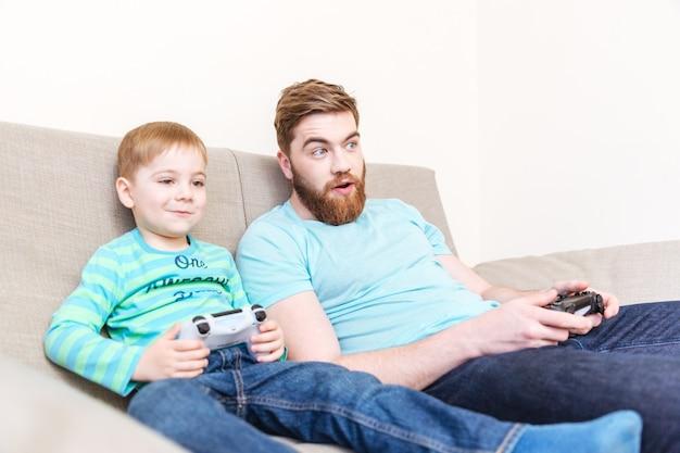 Zdumiony szczęśliwy ojciec grający z synem w gry komputerowe na kanapie w domu