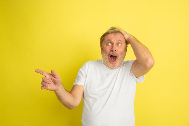 Zdumiony, zszokowany, wskazując w bok. portret kaukaski mężczyzna na białym tle na żółtym tle studio. piękny model mężczyzna w białej koszuli pozowanie. pojęcie ludzkich emocji, wyraz twarzy, sprzedaż, reklama.